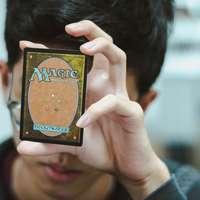 băiat care deține Magic: The Gathering card de tranzacționare