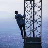 muž lezení na věži poblíž budov ve dne