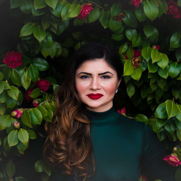 Vrouw dichtbij rode bloemstruik