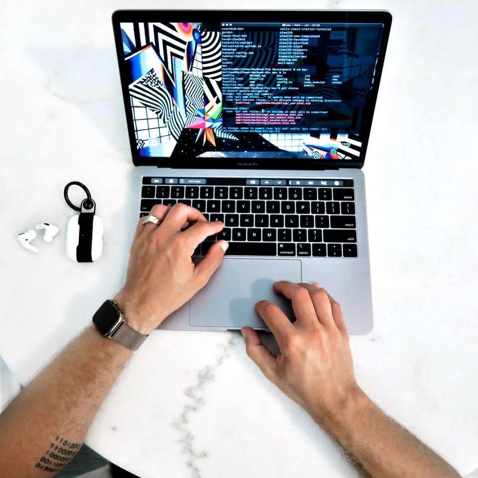 Code bereinigen - Person mit MacBook Pro auf weißem Tisch (8×8)