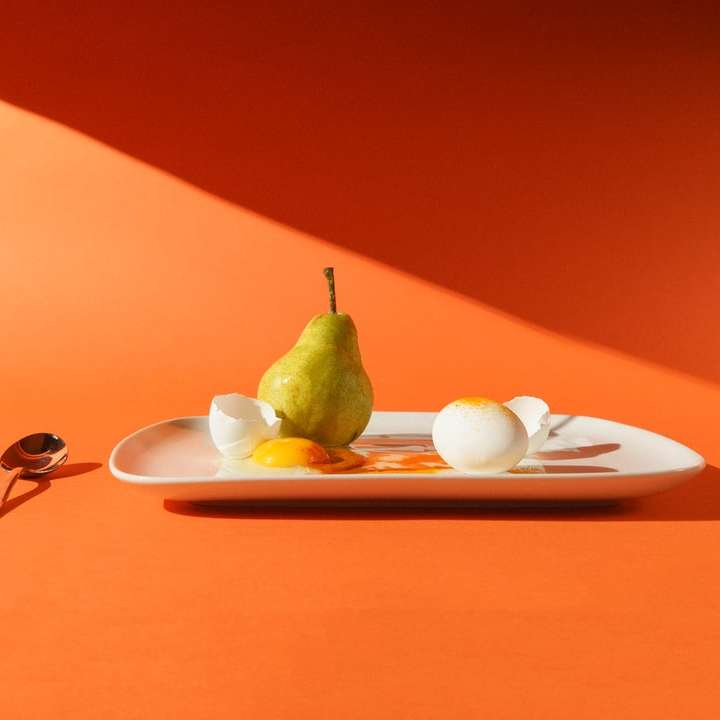 green fruit on white ceramic plate - A pear and eggs with a simple orange background (5×5)
