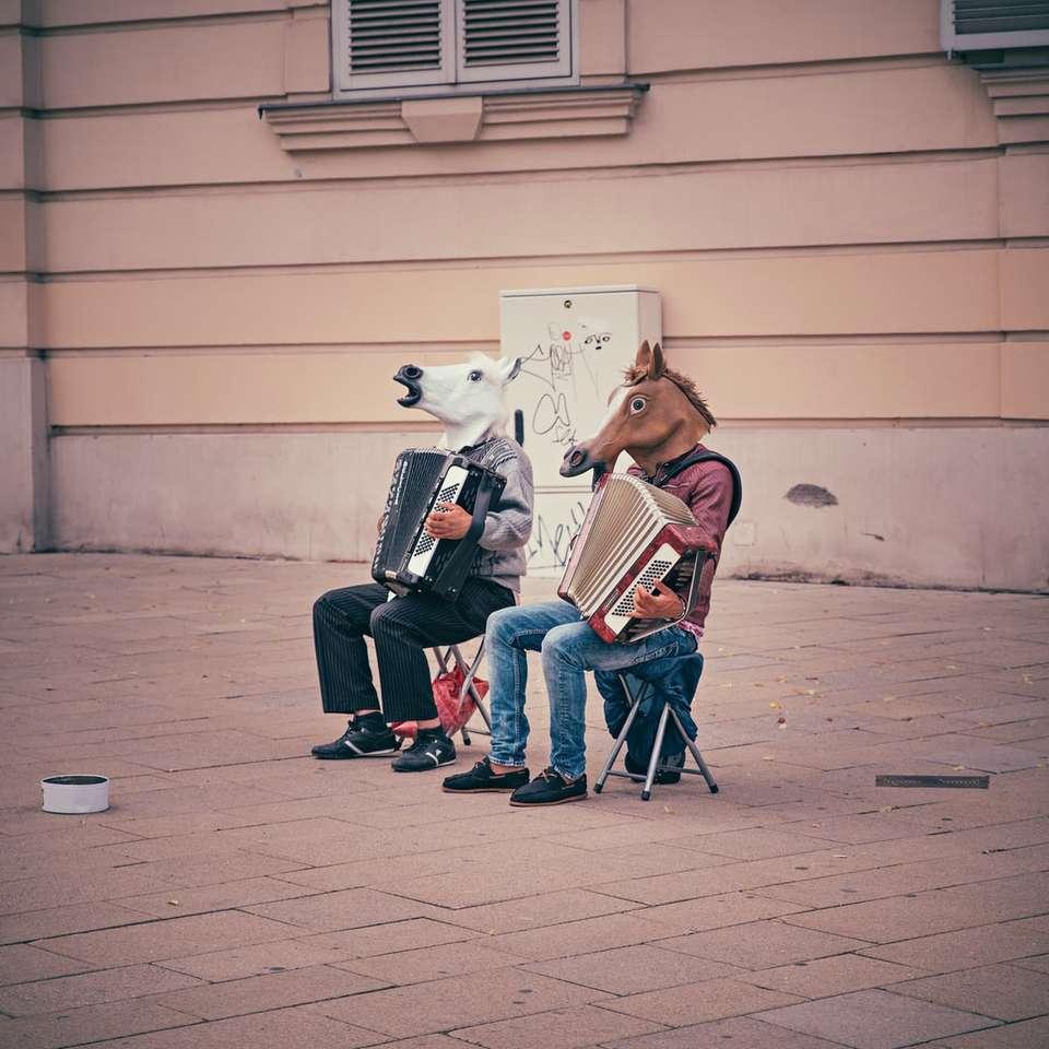 due persone che indossano teste di cavallo seduti su sedie pieghevoli - due persone che indossano teste di cavallo seduti su sedie pieghevoli mentre suonano le fisarmoniche accanto a un edificio di cemento marrone. Ero fuori a fare una passeggiata nel centro di Vienna ed (7×7)