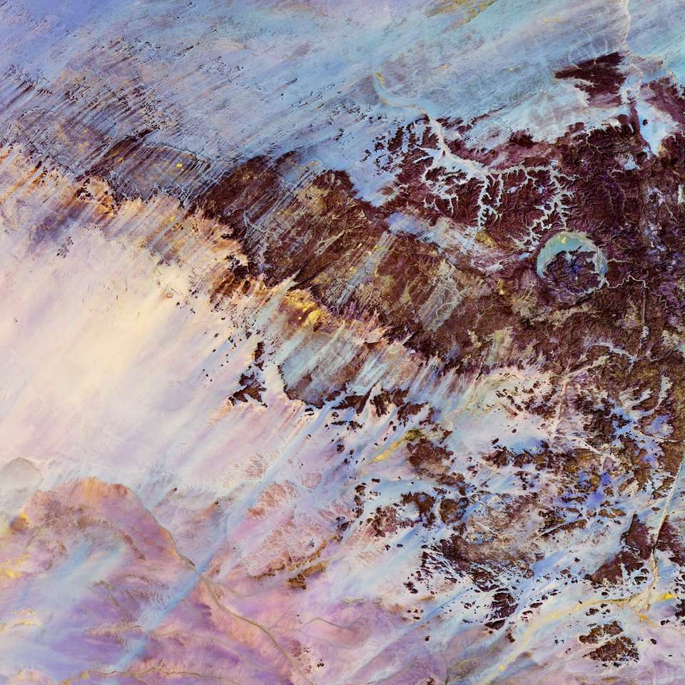 meteorietinslagkrater op het Ennedi-plateau in het noorden van Tsjaad - Zelfs met de kalmerende blauwe tinten is er een verontrustend gevoel in de grillige markeringen die leiden tot een cirkelvormig kenmerk. Deze functie is de Gweni-Fada-krater, een meteorietinslagkrater (3×3)
