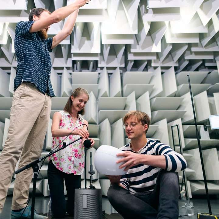 man in black and white striped shirt and brown pants - man in black and white striped shirt and brown pants holding woman in pink shirt. Female noise and vibration engineer sets up microphones to test products with colleagues in anechoic chamber (6×6)
