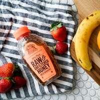 rohe und ungefilterte Honigflasche zwischen Erdbeeren