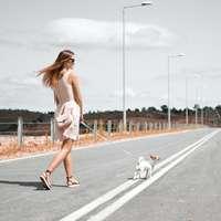 kvinna i vit ärmlös klänning som håller selen av valpen