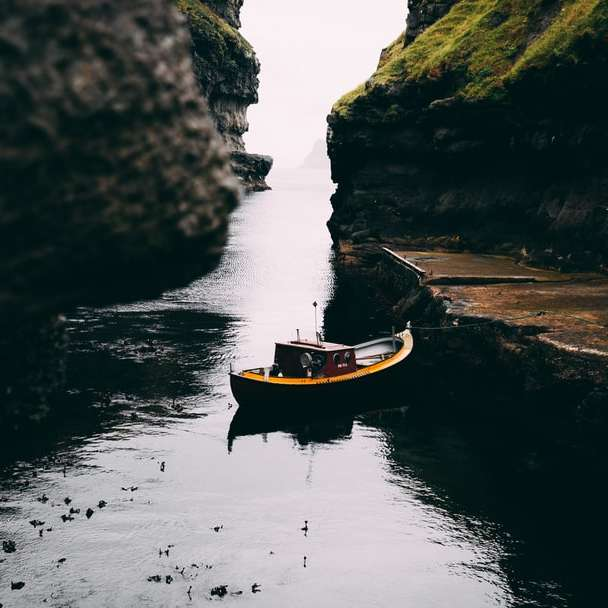 boat on water between rock formations