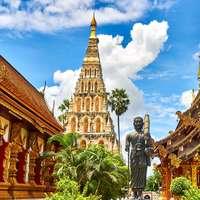 estátua em pé e marco de templos durante o dia