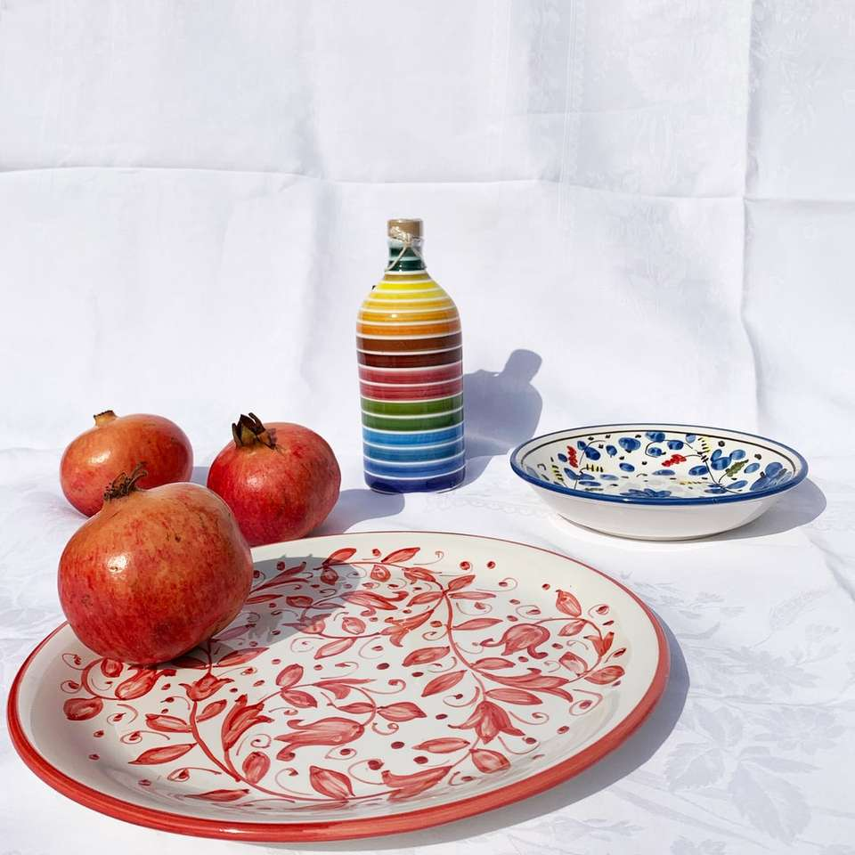 röda äpplen på vit och blå blommig keramisk tallrik