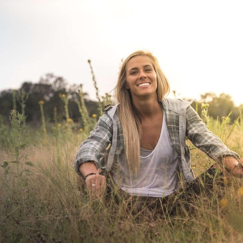 mulher sentada no campo de grama