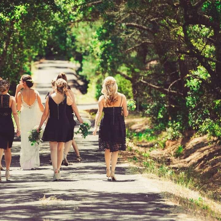 sposa e damigella d'onore che camminano sulla strada tra alberi verdi