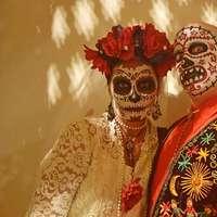 uomo e donna con vernice per il viso in piedi accanto al muro bianco