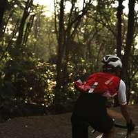 muž v červené košili jedoucí na kole