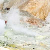 lidé stojící na zelené louky poblíž hnědé hory