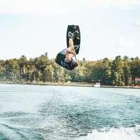 muž v černé bundě a černé kalhoty dělá surfování