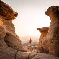 osoba stojící na hnědém skalním útvaru během dne