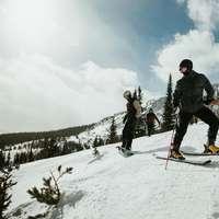 mężczyzna w czarnej kurtce i niebieskich spodniach jadący na nartach