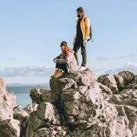 pár sedící na skalním útvaru poblíž vodní plochy