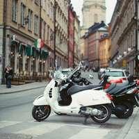 Scooter blanc et noir garé sur le trottoir