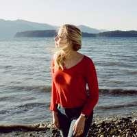 kobieta w czerwonej koszuli z długim rękawem stojącej na skalistym brzegu