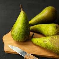 grüne Früchte auf braunem Holzschneidebrett