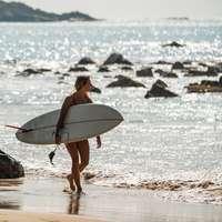 kobieta w czarnym bikini trzymając białą deskę surfingową