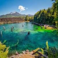 az emberek úsznak a tóban zöld fák és a hegy közelében
