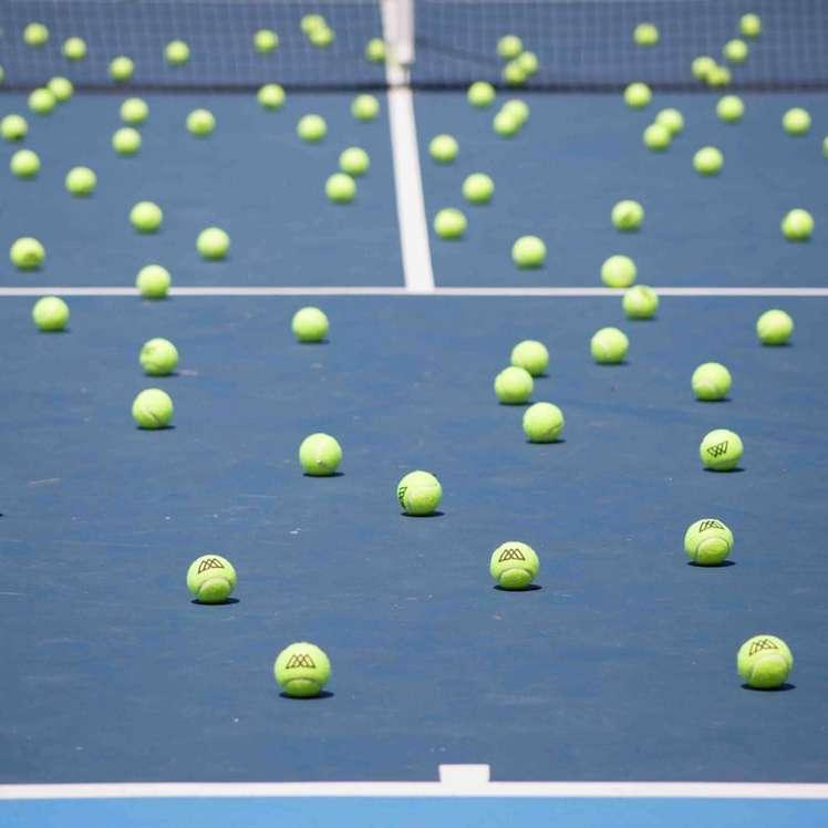 green soccer ball on net - Bunch of tennis balls scattered around blue tennis court (4×4)