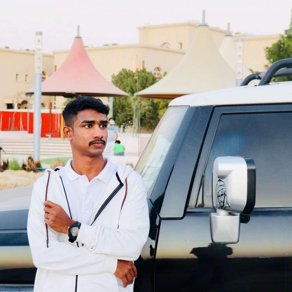 Homme en chemise blanche debout à côté de voiture d'argent - homme en chemise blanche debout à côté de voiture argentée pendant la journée. . Abu Dhabi, Emirats Arabes Unis (7×7)