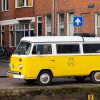 geel en wit volkswagen t-2 busje geparkeerd naast wit betonnen gebouw