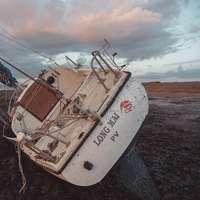 witte en bruine vissersboot aan kust overdag