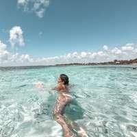 nő piros bikini, napközben úszás a tengerben