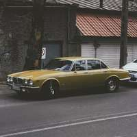 beige sedan on side of road during daytime