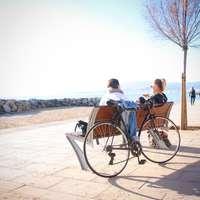 2 Personen sitzen auf Bank mit Fahrrad gelehnt