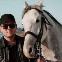 homem de jaqueta de couro preta parado ao lado do cavalo branco
