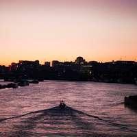 személy lovaglás hajón a víz közelében a város épületei
