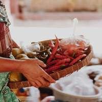 Frau im roten und weißen Kleid, die roten Chili hält