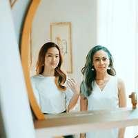 2 vrouwen in wit mouwloos overhemd zittend op stoel