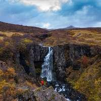 cascadas en la montaña rocosa marrón bajo el cielo nublado blanco