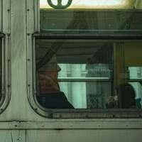 mężczyzna w czerwonej kurtce stojący przed oknem pociągu