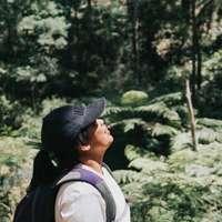 man i svart hatt och vit skjorta som står nära gröna träd