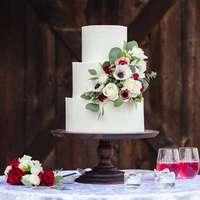 vita och röda rosor på vit kaka med tre nivåer
