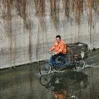 uomo in maglietta polo arancione in sella a una bicicletta blu