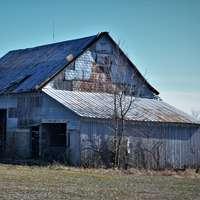кафява дървена къща на поле със зелена трева през деня