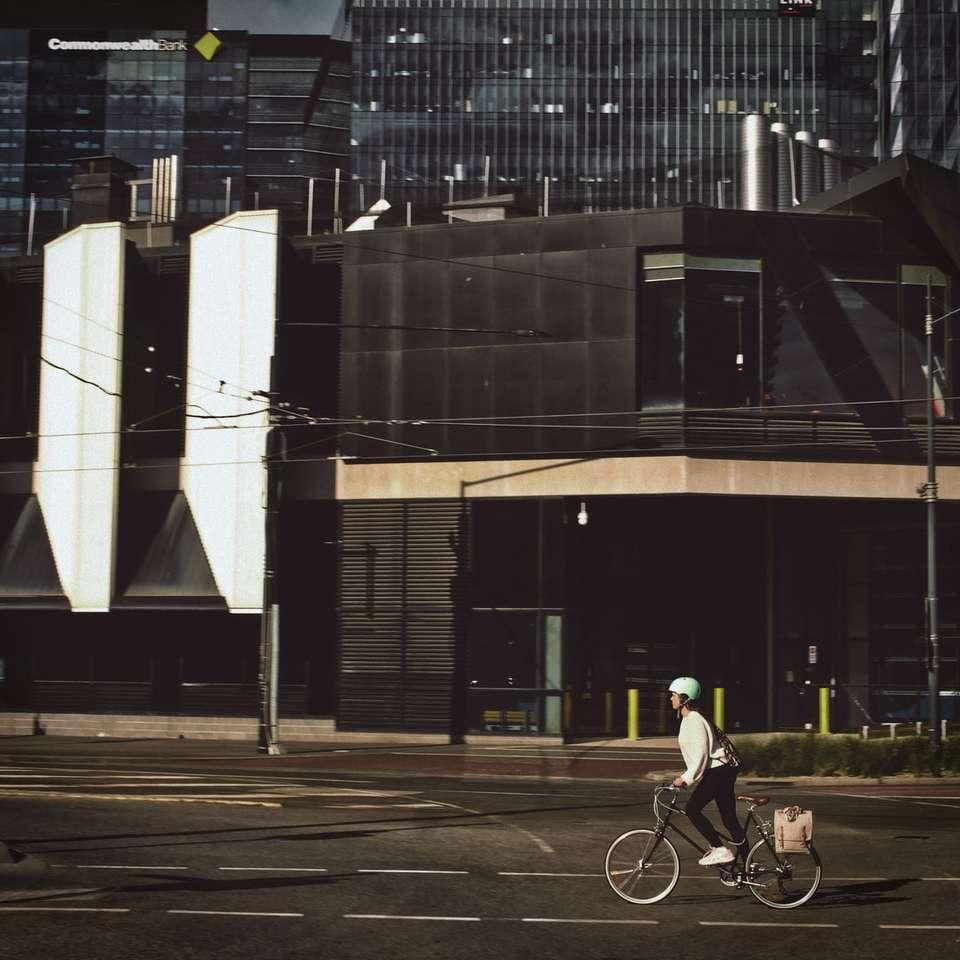 Mann im schwarzen Hemd, das Fahrrad auf Straße nahe Gebäude fährt