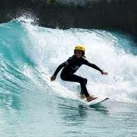 mężczyzna w czarnym kombinezonie, jazda na żółtej desce surfingowej na wodzie