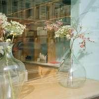 Flores blancas y rosadas en jarrón de cristal transparente.