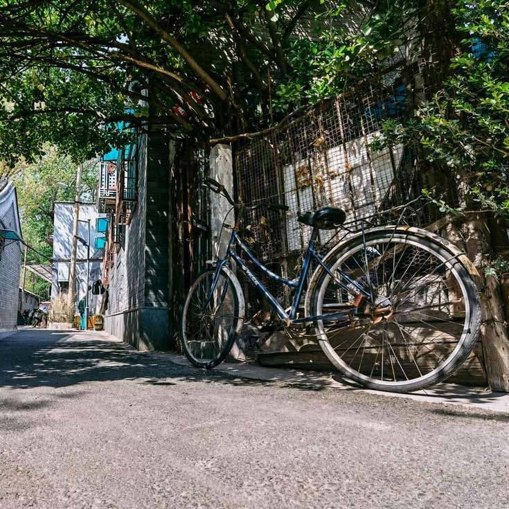 black city bike parked beside gray concrete wall sliding puzzle