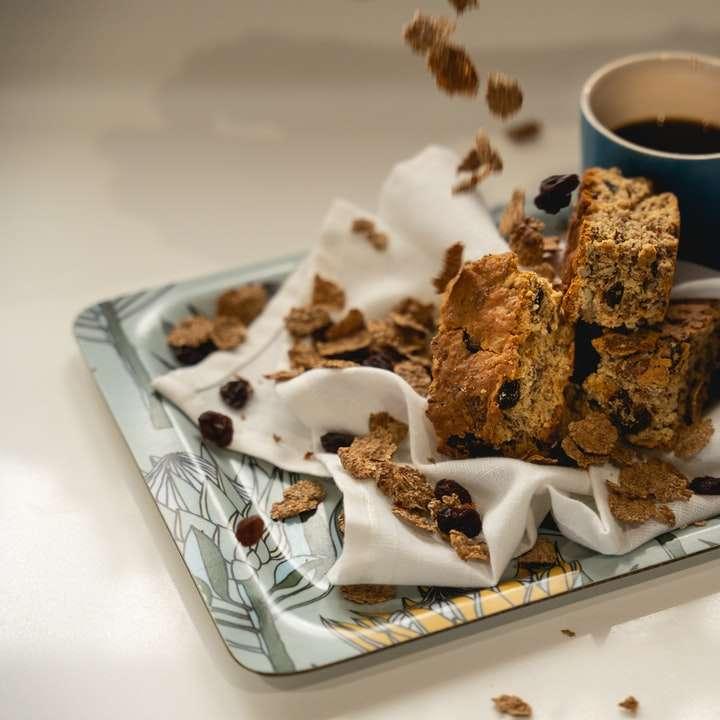 brown cookies on white ceramic plate beside blue ceramic mug sliding puzzle