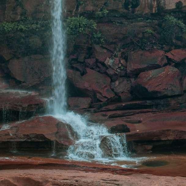 man in yellow jacket standing on brown rock near waterfalls